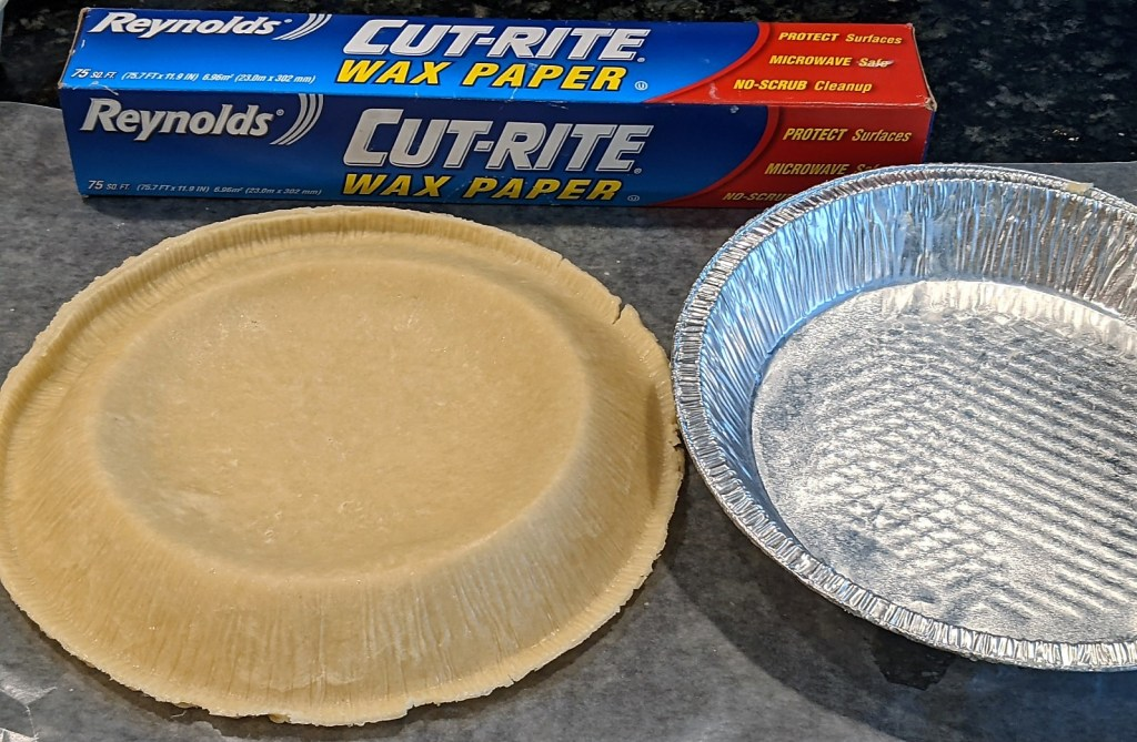 Pie crust removed from pie pan on waxed paper