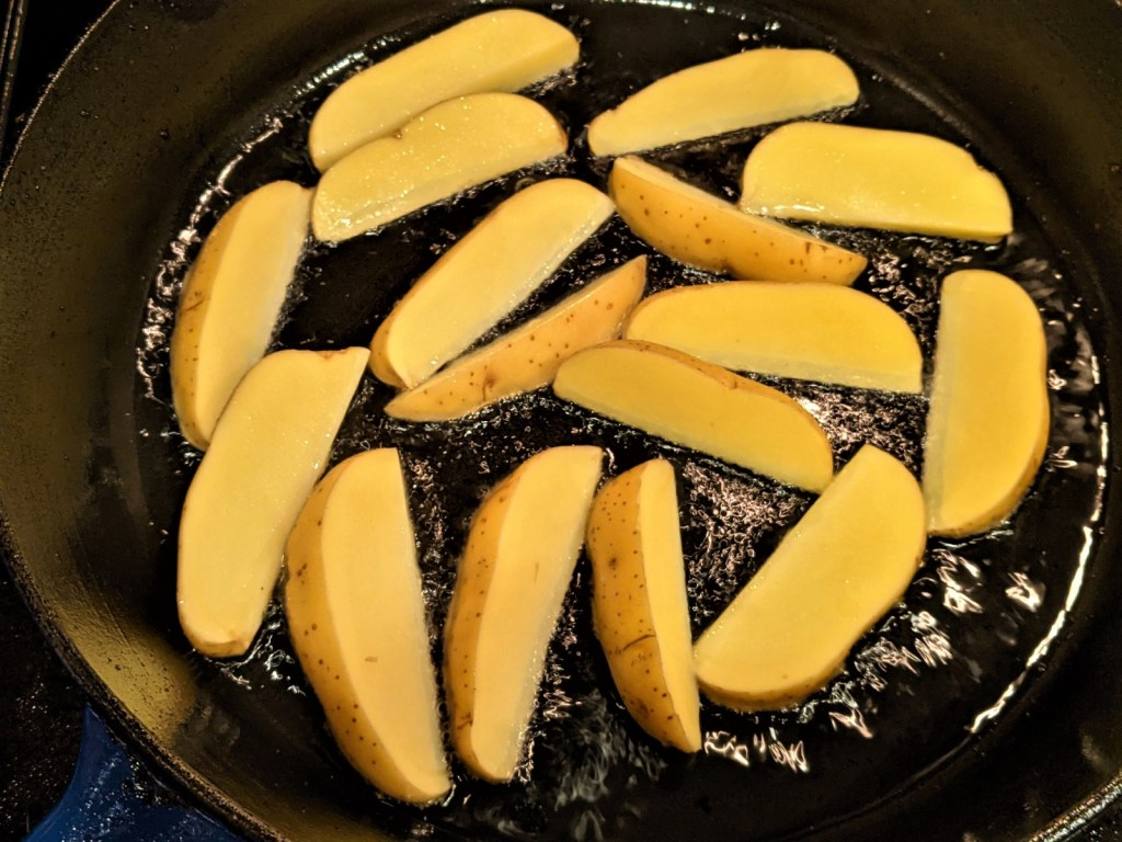 wedges of potato in pan