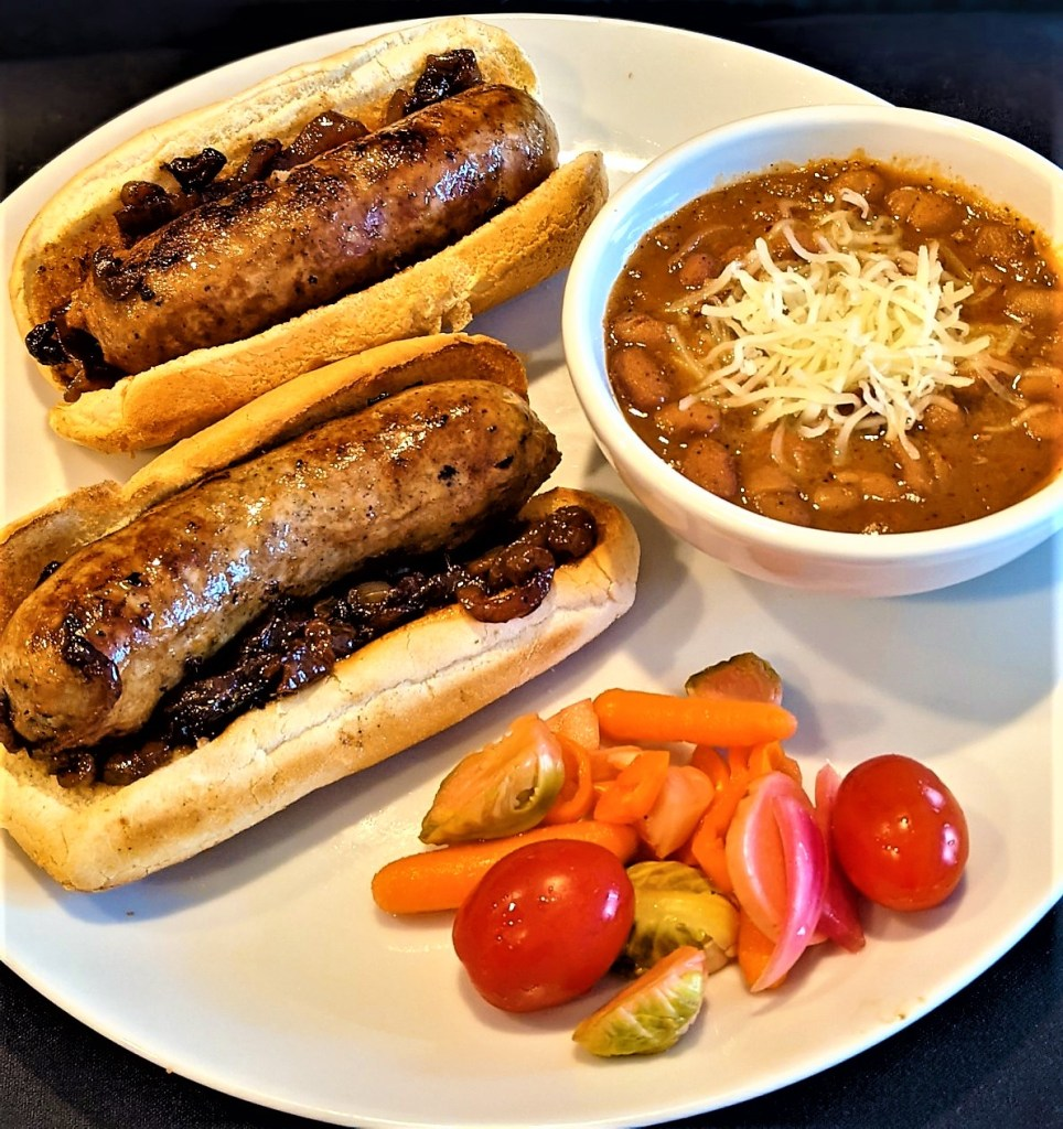 Brats, beans and garnish on a plate