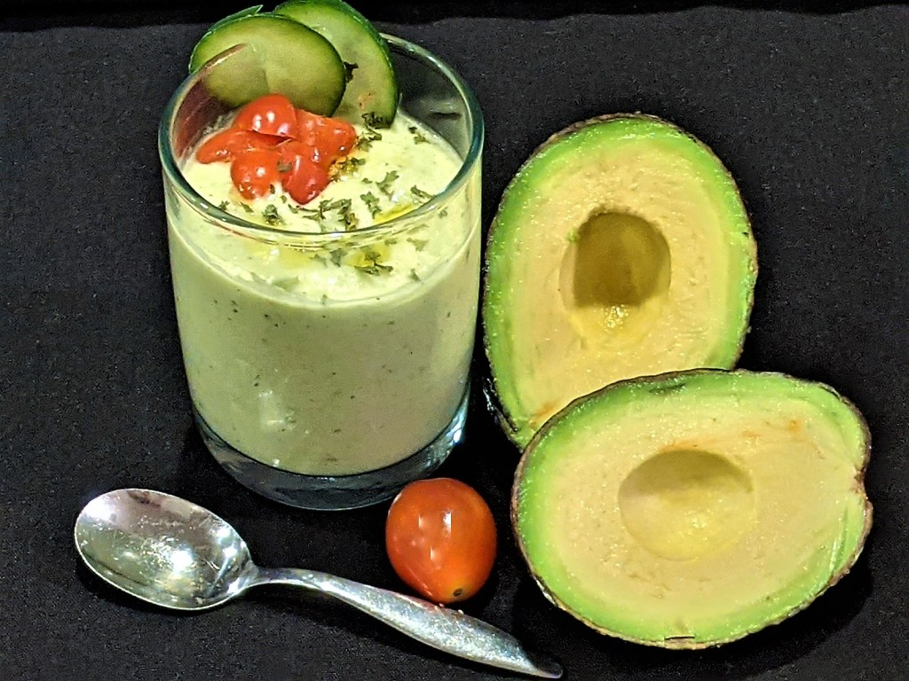 Soup in a cup with image of avocado, tomato and spoon.