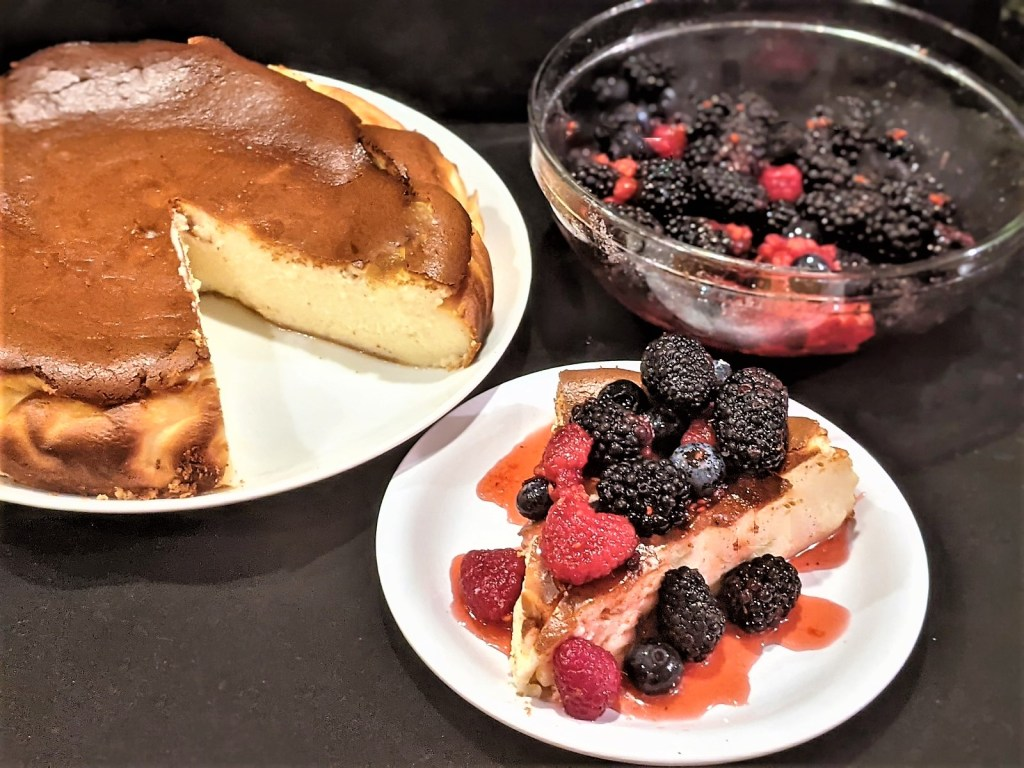 Cheesecake on a plate, a slice of cheesecake topped with berries and the bowl of berries
