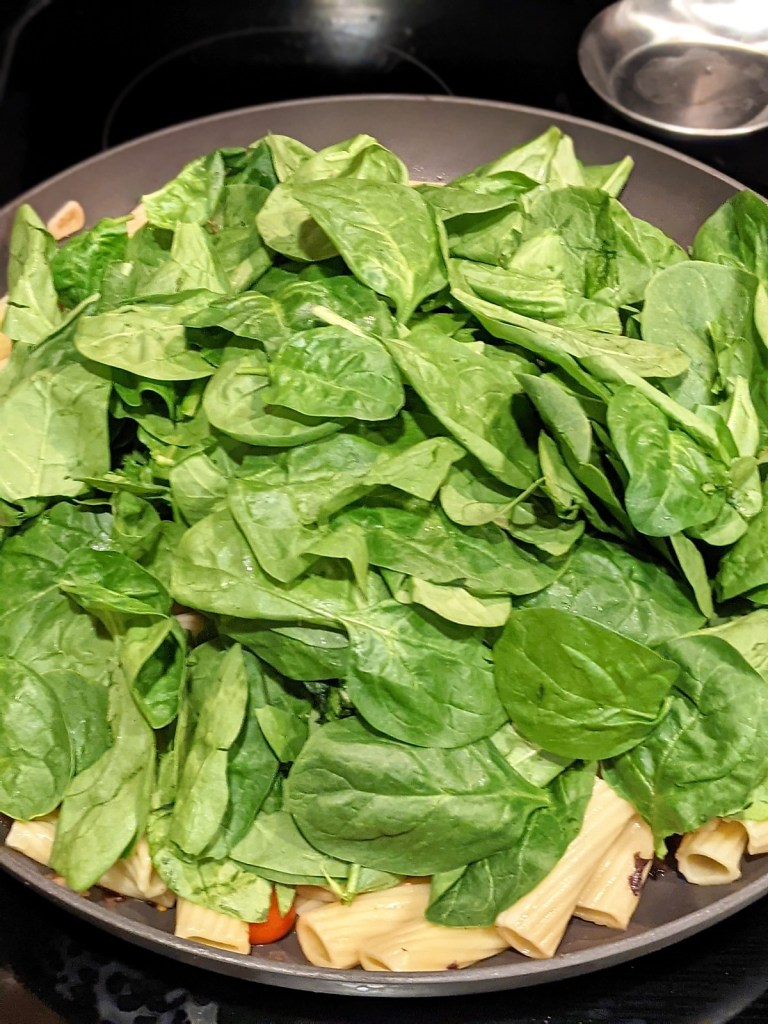 Skillet with pasta and spinach added