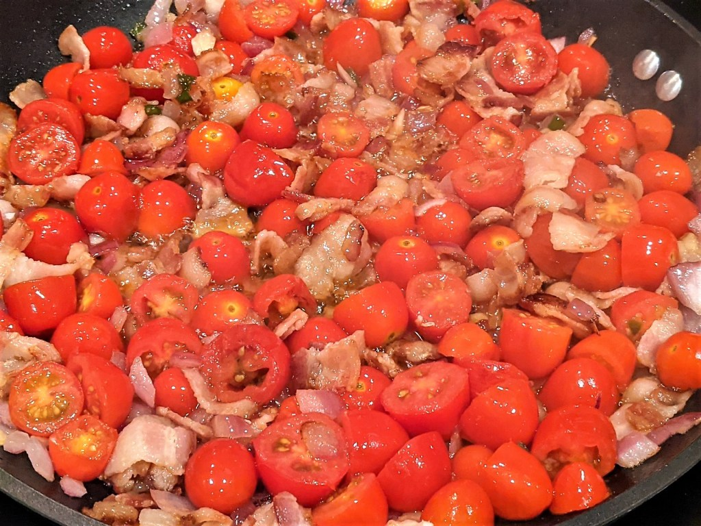 tomatoes cooking in pan with bacon and veggies