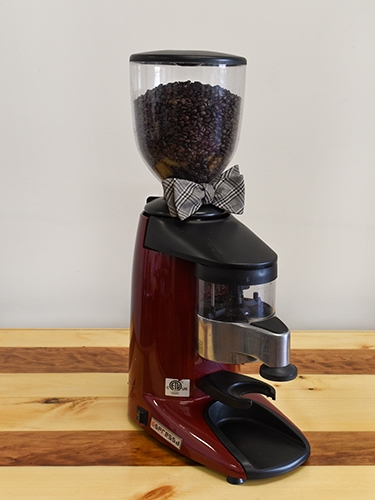 A red espresso machine with a bow tie