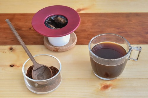 Brewed coffee and a coffee brewing apparatus with ground coffee and a coffee scoop