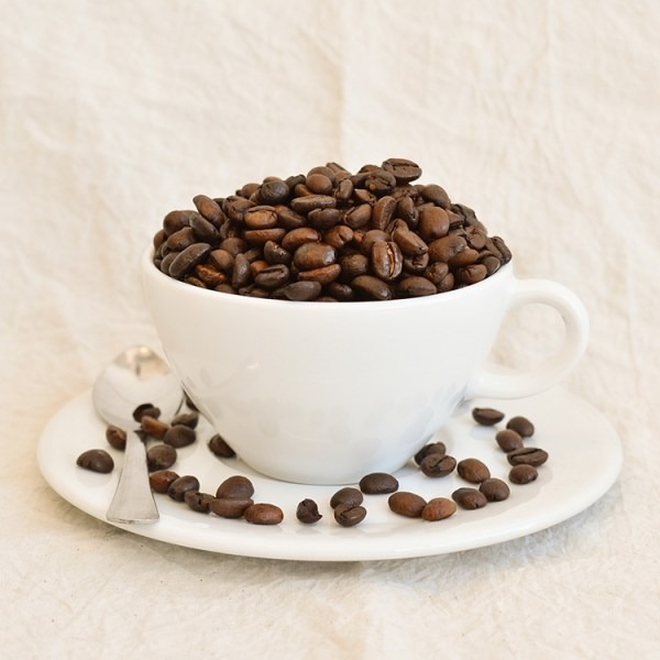 Coffee bean in a white cup on a saucer