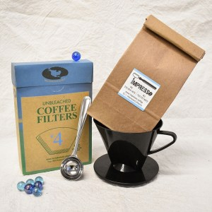 A set of coffee bean, coffee dripper cone, a box of coffee filter and a metal coffee scop