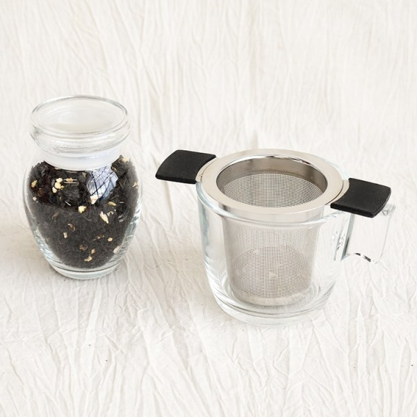 Earl grey tea leaves in a jar and an empty glass with a tea strainer