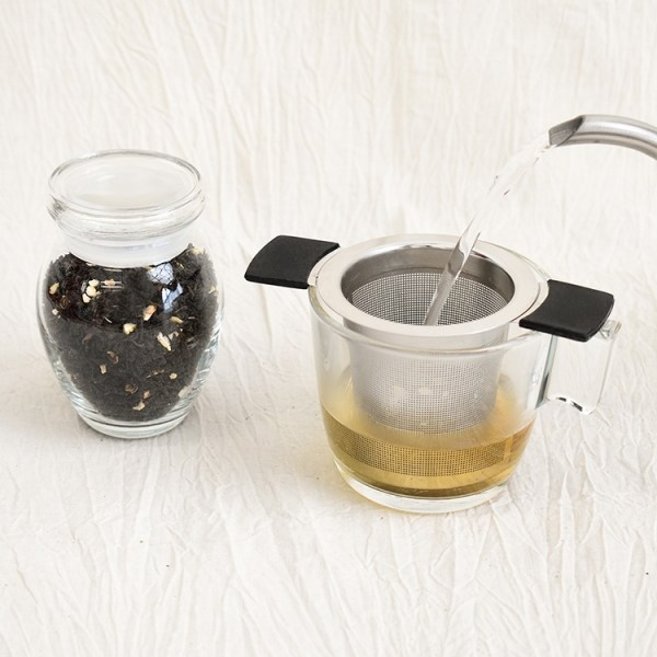 Earl grey tea leaves in a jar, earl grey tea brewing in a glass