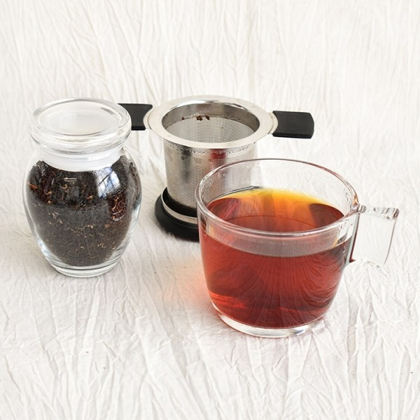 English breakfast tea leaves in a jar, english breakfast tea in a glass, used tea strainer in the background