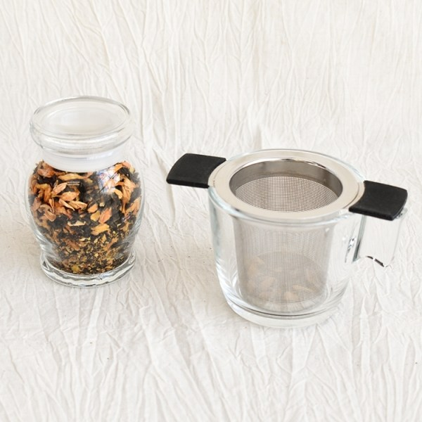 Jasmine green tea leaves in a jar and an empty glass with a tea strainer