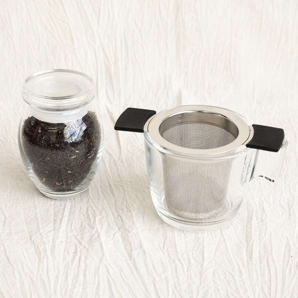 Mangalam black tea leaves in a jar and an empty glass with a tea strainer