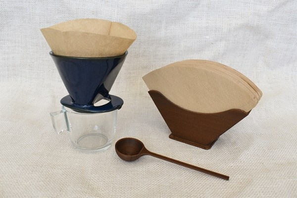 A set of coffee filter, filter holder and coffee scoop with a blue coffee dripper on top of an empty glass