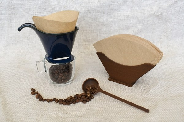 A set of coffee filter, filter holder and coffee scoop with a blue coffee dripper and a glass filled with coffee beans