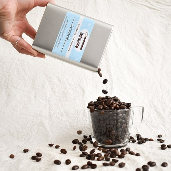 Large tin with coffee beans spilling into a glass