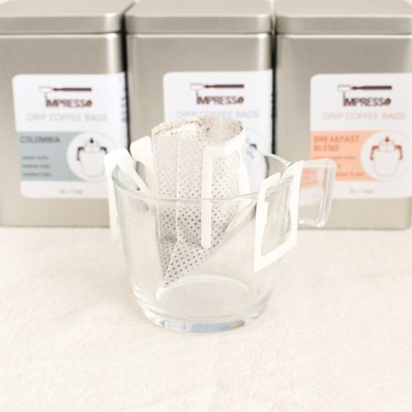 Drip coffee bag sitting on a glass