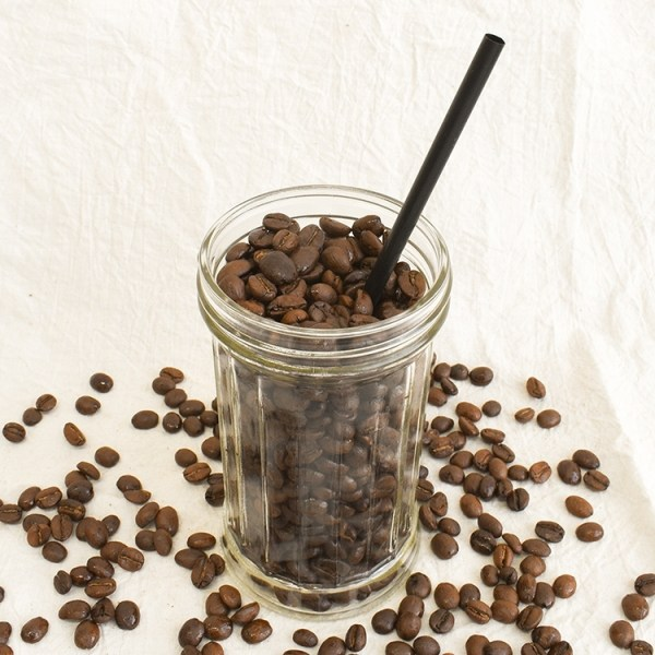 Coffee bean in a glass with a straw