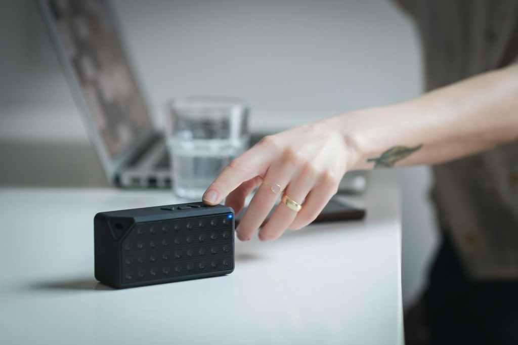 rectangular black speaker on white wooden surface