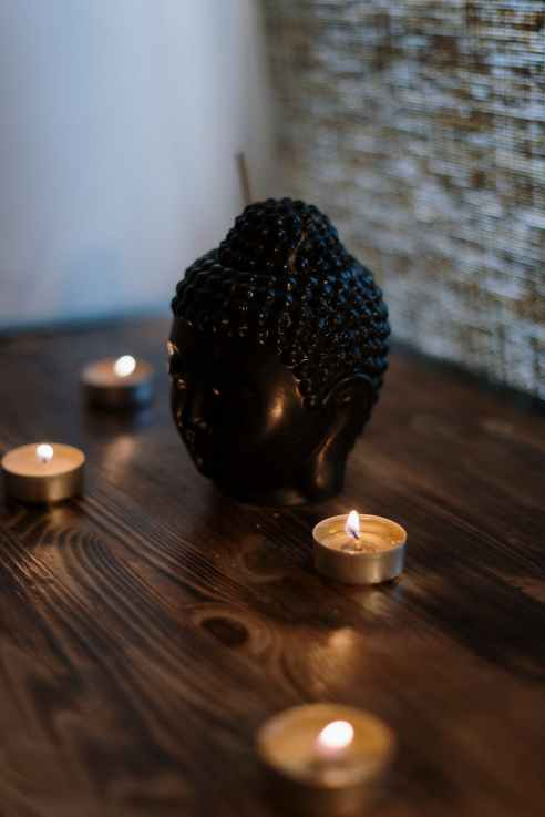 black ceramic candle holder on brown wooden table