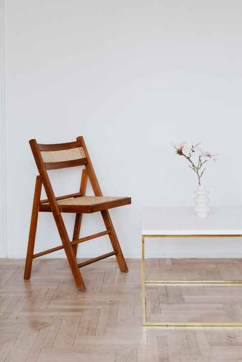 wooden chair near table with flower in white vase