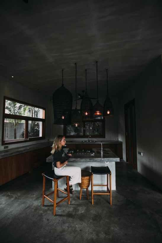 melancholic woman resting on stool in dark kitchen