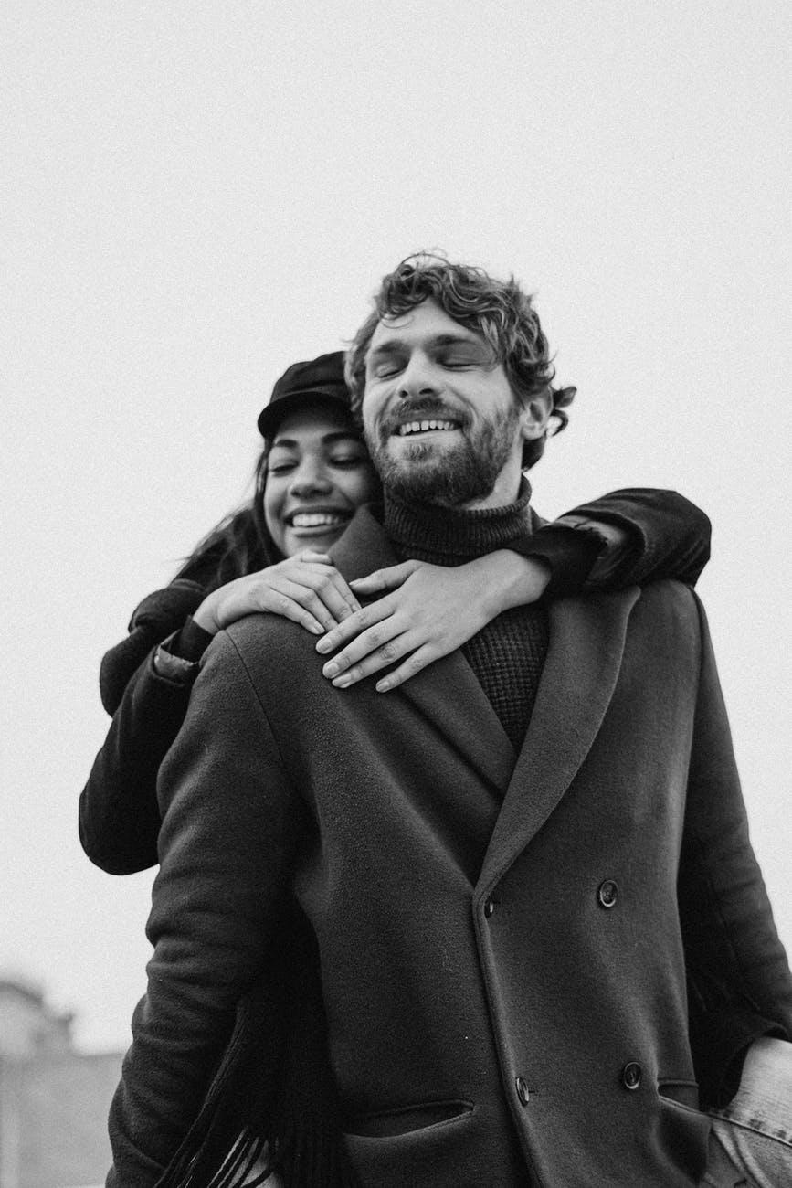 woman hugging man wearing black coat
