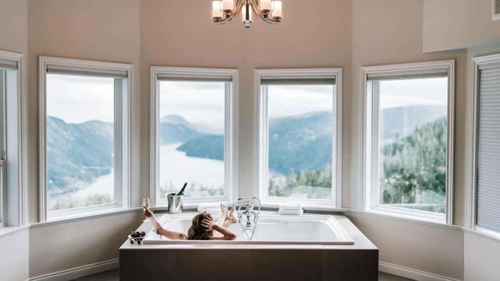 woman in bathtub near windows