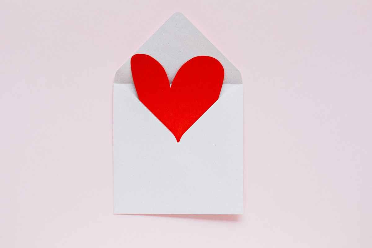 open envelope with heart made of colored carton