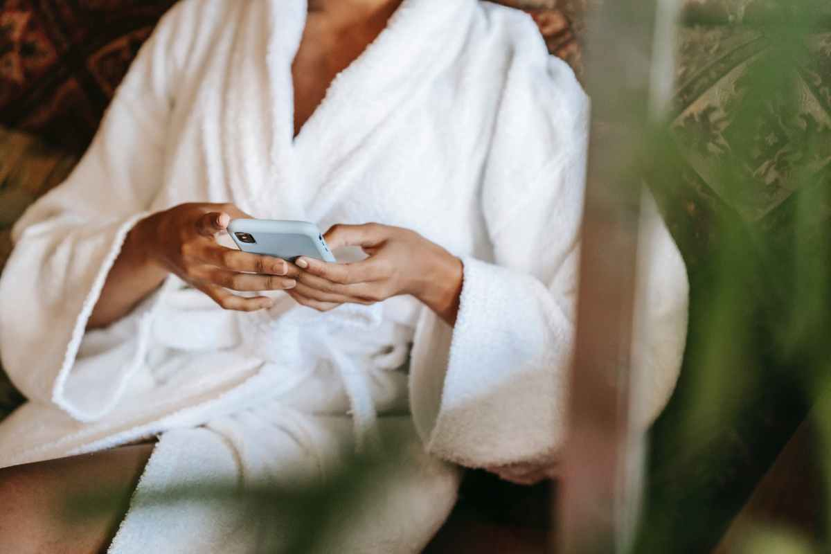 crop ethnic woman chatting on smartphone in spa center