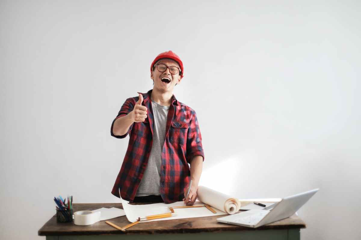laughing male constructor showing thumb up at working desk