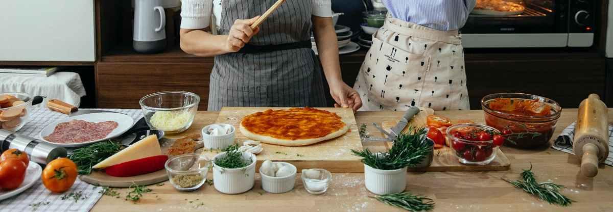 crop chefs preparing pizza in kitchen at home