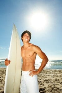 Man with a surfboard gets a portrait taken on the beach.