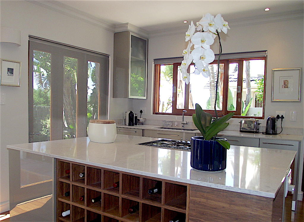 Kitchen remodel with stone top island with gas cooker and wine storage in veneer