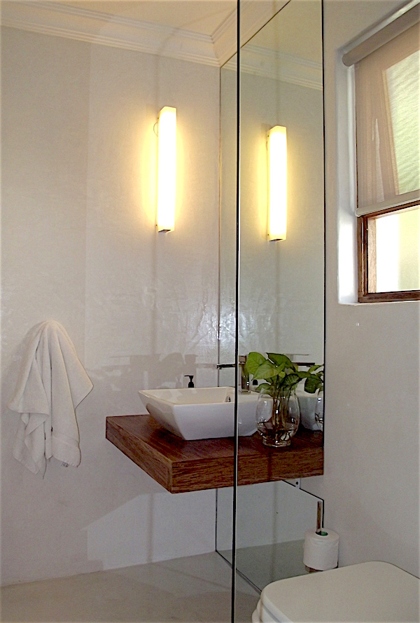 Powder room with full-height mirror and floating timber vanity