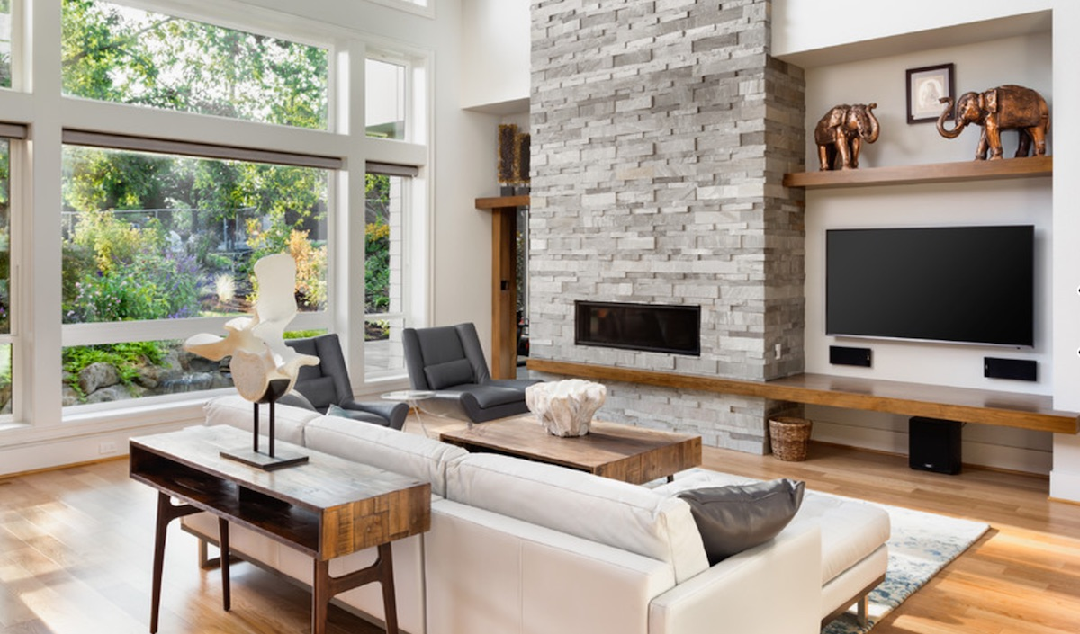 TV next to stone fireplace with timber shelves