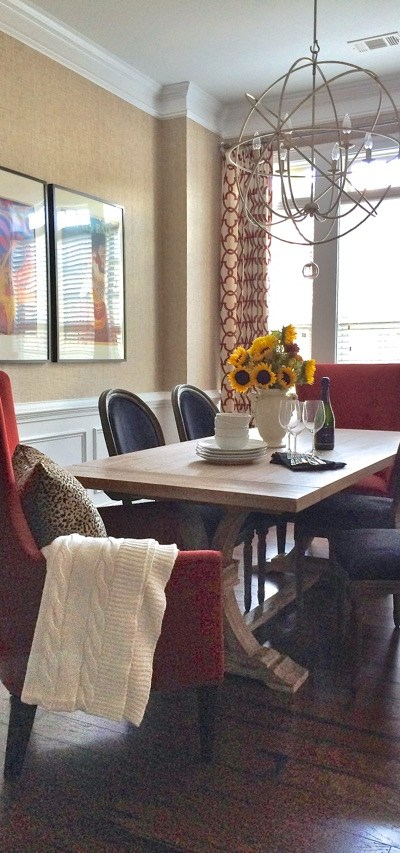 A pair of lorldly end chairs in red to the dining table with period chairs