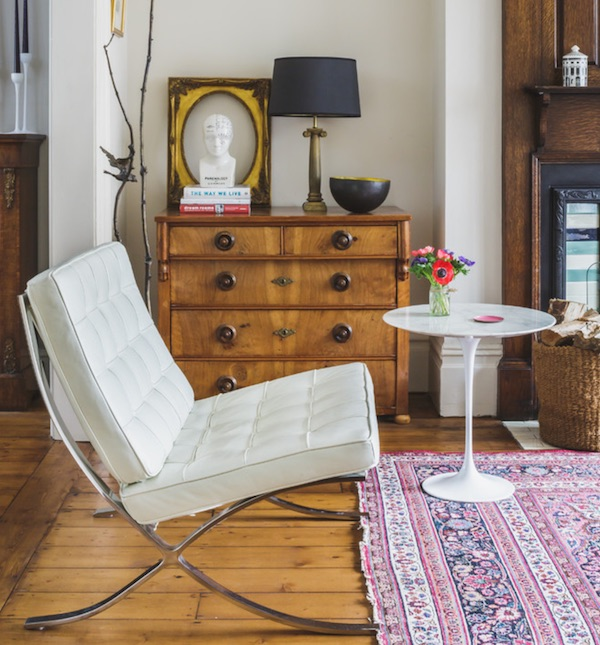 Barcelona chair next to antique chest of drawers and worn Persian rug