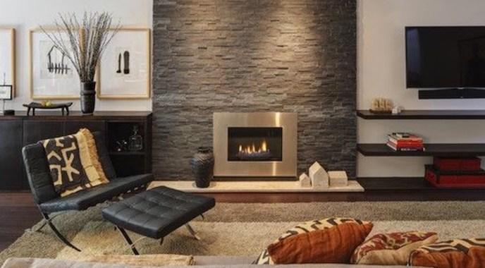 tv alongside stone fireplace in living room