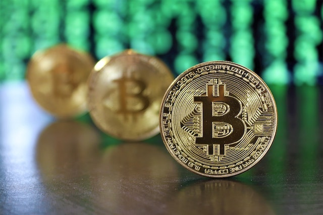 Three bitcoins standing upright on table