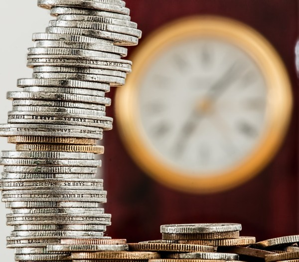 IT costs: pile of coins with blurred clock in background