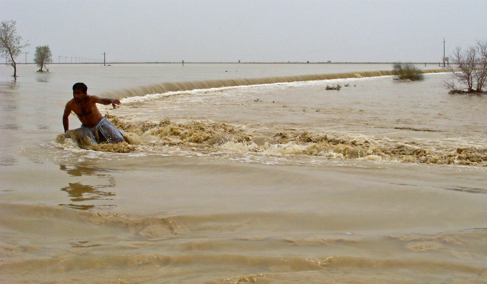 A Pakistani villager struggles to reach his village through a fast-moving flood water caused by heavy monsoon rain in Bakhtiarabad, 250 km (155 mi) north of Quetta, Pakistan on Friday, July 23, 2010. (AP Photo/Fida Hussain)
