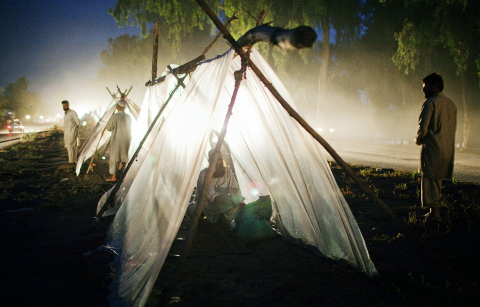 Families set in for the evening in their makeshift tent homes located on a median strip after having abandoned their flood-destroyed homes, on August 3, 2010 in Pabi, Pakistan. (Daniel Berehulak/Getty Images)