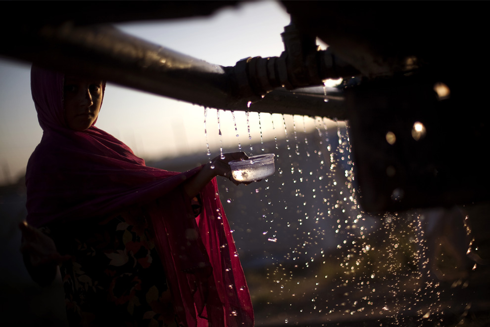 A young girl collects water from a truck