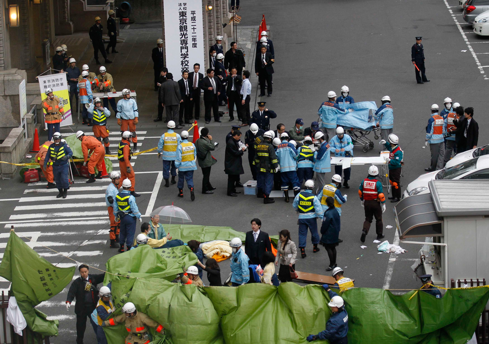 Rescue workers hurry to a building following reports of injuries in Tokyo's financial district after an earthquake hit off the coast of northern Japan. There were several strong aftershocks and a warning of a 10-metre tsunami following the quake, which also caused buildings to shake violently in the capital Tokyo. (Kim Kyung-Hoon/Reuters) #