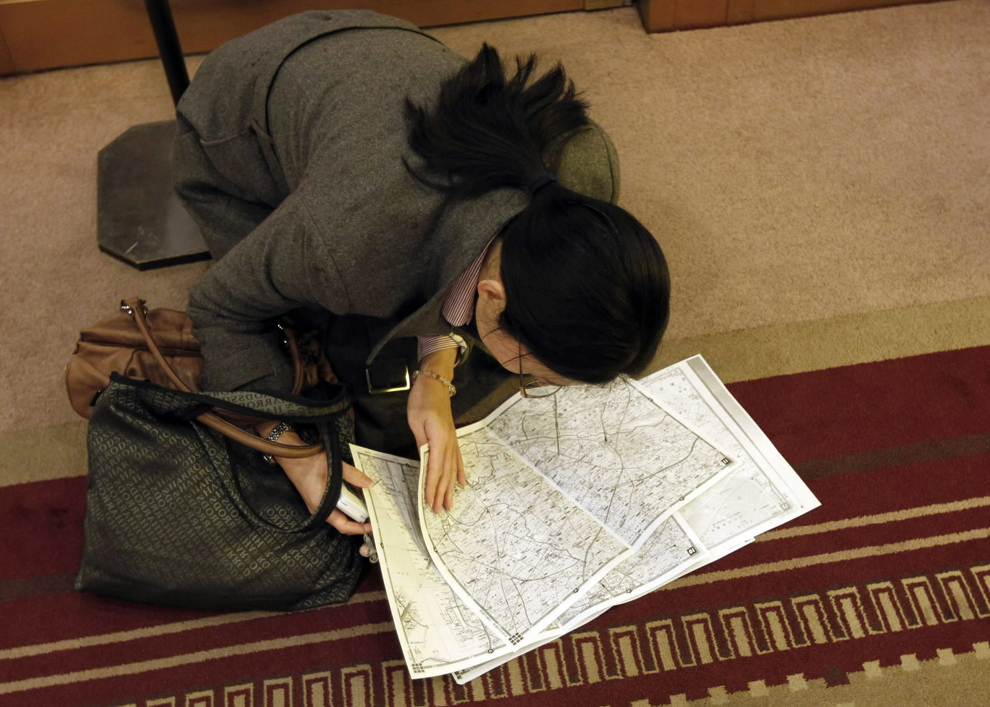 A woman checks a map to find a route as she takes a rest at a hotel lobby after subway and train services were suspended after an earthquake, in Tokyo. (Kim Kyung-Hoon/Reuters)