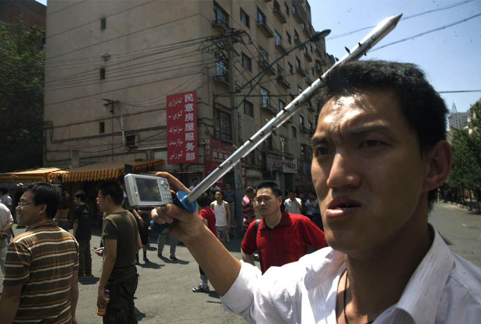A Han Chinese man carries a spiked steel bar while using his cell phone to take photos as he joins a mob of Han Chinese men attacking Uighur properties in Urumqi on Tuesday, July 7, 2009. (AP Photo/Ng Han Guan)