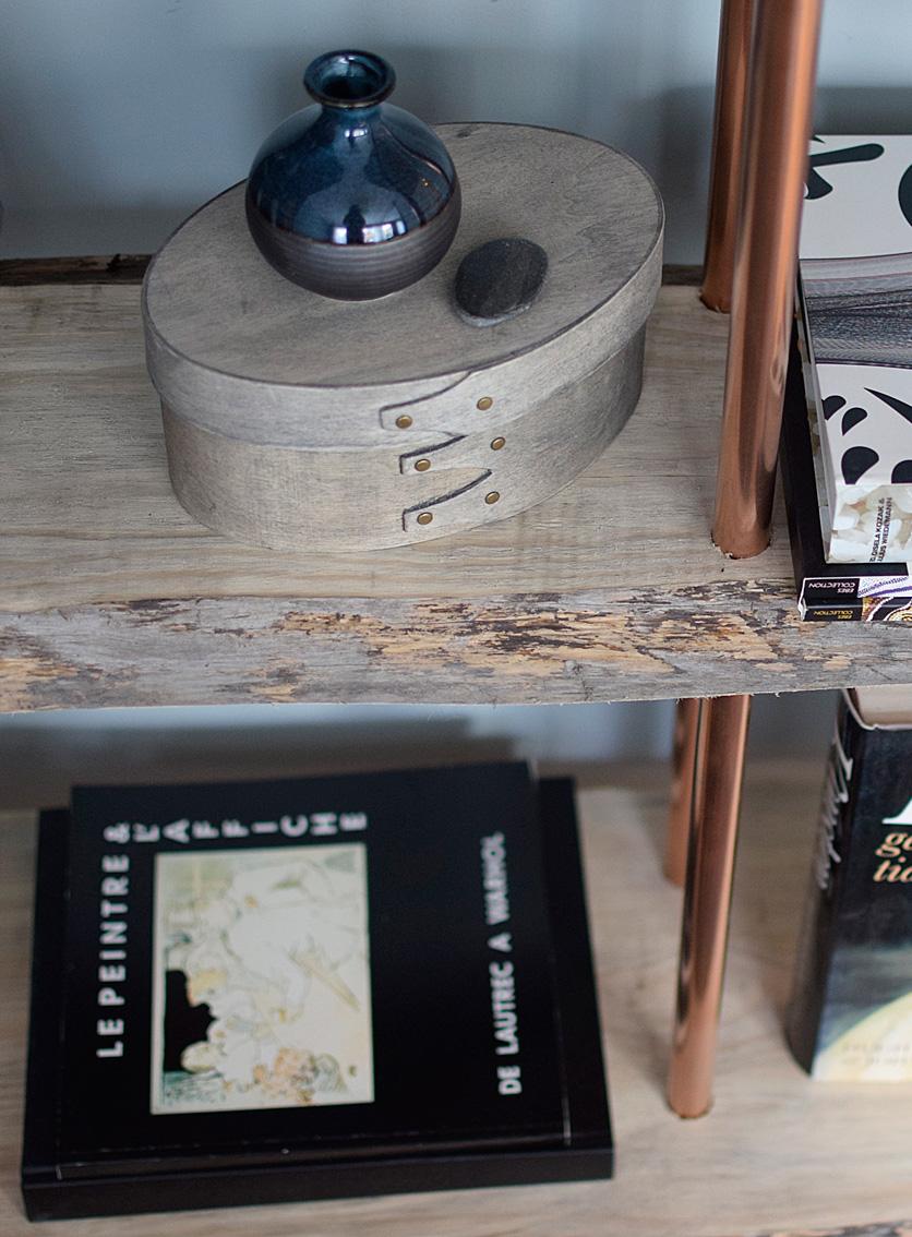 Vi byggde en ny bokhylla med kopparrör och återvunna plankor från båtbygge. Återvinning.