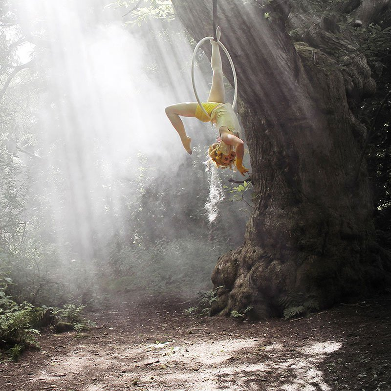 In-between book-your-warrior-guide -Kate George hangs from a trapeze hoop in a forest