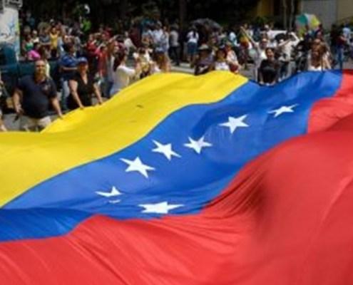 L'immagine evidenzia una grande bandiera del Venezuela tesa tra le mani di un grande folla in mezzo alla strada.