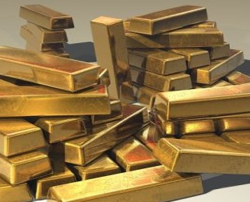 The picture highlights a pile of gold bars stacked randomly on top of each other on a white shelf.